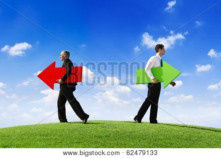 Two Businessmen Holding Contrasting Arrows Going Seperate Ways