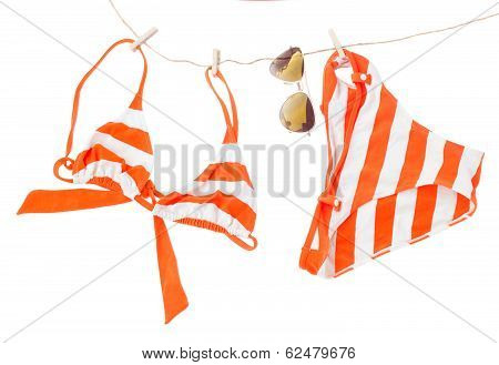 swimming suit with glasses hanging on rope
