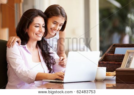 Mother And Teenage Daughter Looking At Laptop Together