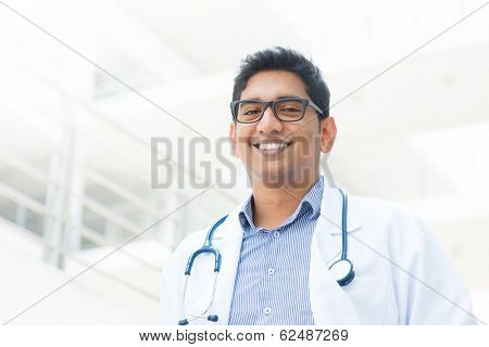 Portrait of a smiling Asian Indian male medical doctor in uniform, hospital building at background.