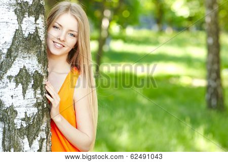 Beautiful female peeping from behind tree