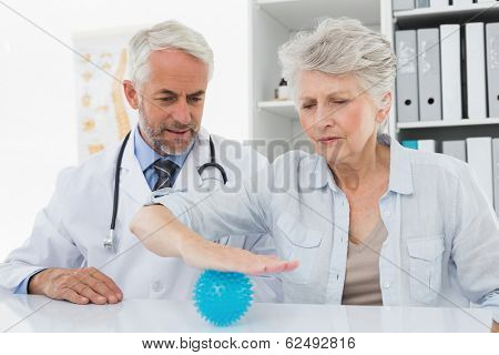 Male doctor with senior patient using stress buster ball at the medical office