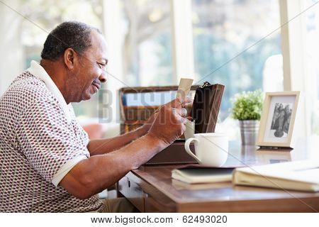 Senior Man Putting Letter Into Keepsake Box