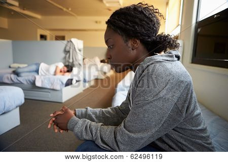 Women Sitting On Beds In Homeless Shelter