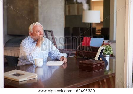 Senior Man Writing Memoirs In Book Sitting At Desk