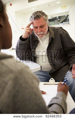 Man Talking To Counsellor Who Takes Notes