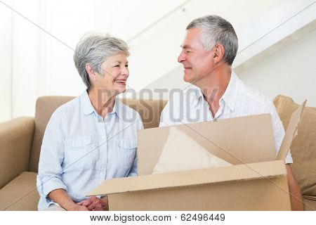 Cheerful senior couple moving into new home smiling at each other