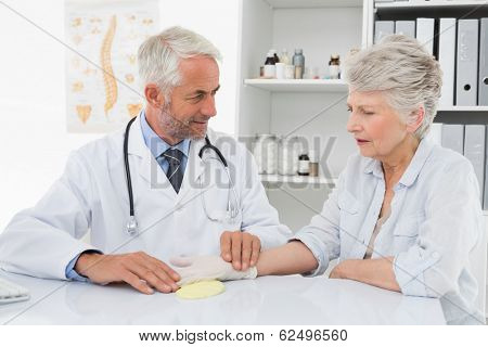 Male doctor taking a senior female's pulse at the medical office