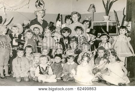 LODZ,POLAND, CIRCA 1970's: Vintage photo of group of little children and teachers posing together during a costume party in nursery school