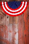 stock photo of rosettes  - Independence Day patriotic rosette to commemmorate the signing of the Declaration of Independence on the 4th July lying on rustic wooden boards with plenty of copyspace in vertical format - JPG