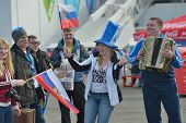SOCHI, RUSSIA - FEBRUARY 12, 2014: Russian fans with national flags sing the song in Olympic Park du