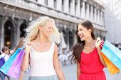 stock photo of piazza  - Shopping women happy holding shopping bags walking having fun laughing - JPG