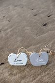 stock photo of quicksand  - two inscribed wooden love hearts sinking in the quicksand on a wild Atlantic way Irish beach in summer - JPG