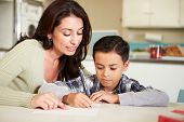 stock photo of homework  - Hispanic Mother Helping Son With Homework At Table - JPG