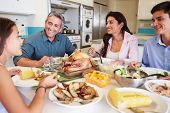 stock photo of 16 year old  - Family Sitting Around Table At Home Eating Meal - JPG