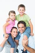 Parents giving their children piggyback ride smiling at camera on white background