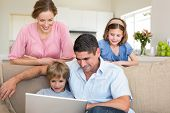 Father with boy using laptop while girl and mother watching them in living room