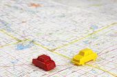 image of intersection  - Game piece cars of red and yellow intersecting on a map - JPG