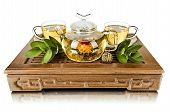 image of teapot  - still life of the glass teapot flow green tea in cup on wooden trivet white background isolated tea ceremony - JPG