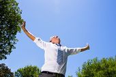 Low angle view of carefree businessman with arms outstretched standing against blue sky