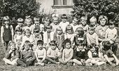 LODZ,POLAND, CIRCA 1960's: Vintage photo of group of little classmates and teacher posing together o