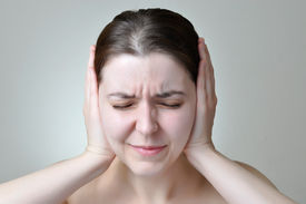 stock photo of noise pollution  - Young woman covering her ears with her hands - JPG