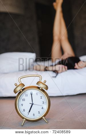Big alarm clock in the foreground. Morning in a bed.
