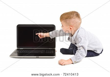 Cute boy points finger at the screen of laptop