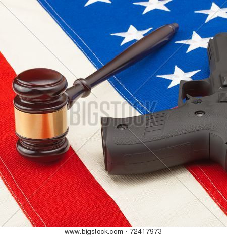 Wooden Judge Gavel And Gun Over Us Flag - Studio Shot