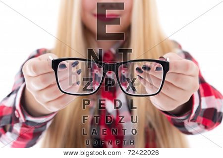 Modern Black Eyeglasses In Female Hands And Eye Test Chart
