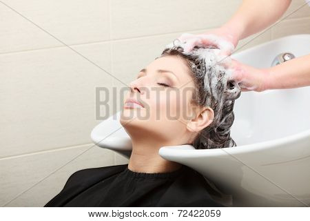 In Hairdressing Salon. Hairstylist Washing Hair Woman Client.