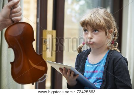 Young Girl Would Rather Play On Digital Tablet Than Practise Violin