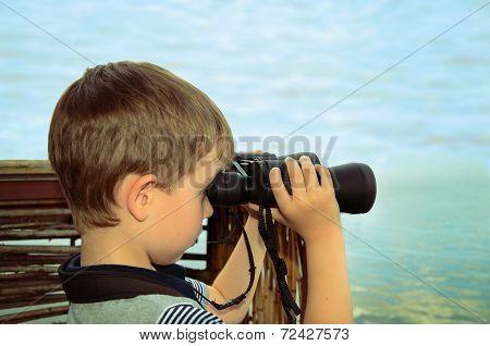 Little Boy Looking Through Binoculars At Sea. Side View, Toning Effect