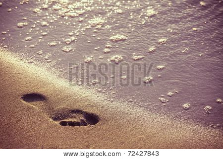 Retro Picture Of Beach, Water And Footstep At Sunset.