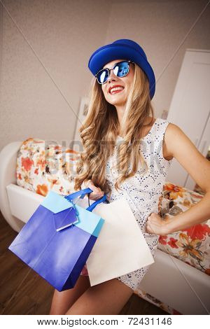 girl in a blue hat and glasses with bags