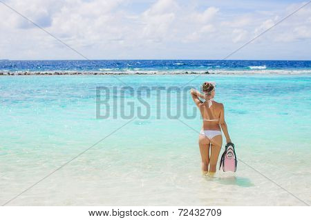 Happy woman with snorkeling equipment on the beach