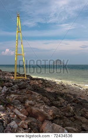 View on a small island from the rocky shore with a lighthouse in Thailand