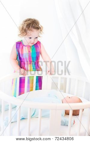 Adorable Laughing Toddler Girl Standing At A White Round Bed Of Her Newborn Baby Brother