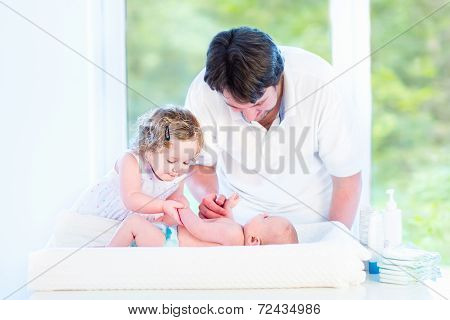 Cute Newborn Baby Looking At His Father And Toddler Sister Changing His Diaper