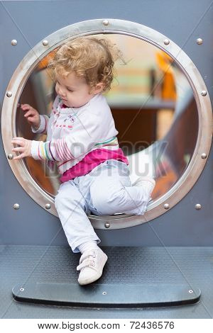 Sweet Curly Baby Girl Sliding On A Playground