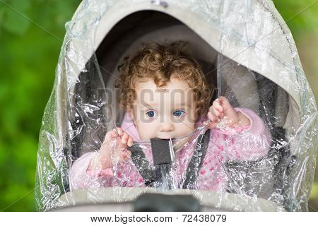 Cute Curly Baby Girl Sitting In A Stroller Under A Plastic Rain Cover On A Cold Autumn Day