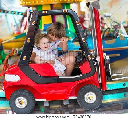 Brother And Little Baby Sister Enjoying A Ride In An Amusement Park