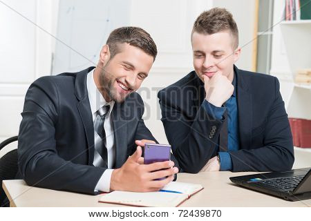 Waist-up portrait of two handsome businessmen in suits