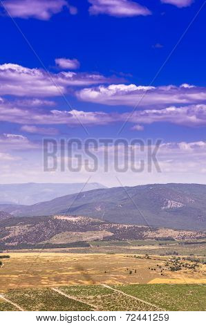 Views Of The Mountain Range With Snow-white Clouds On A Blue Sky