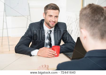 Portrait of two handsome businessmen in suits having a coffee-br