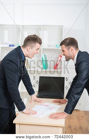 Portrait of two angry businessmen in suits standing near the tab