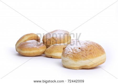 Donuts topped with powdered sugar on a white