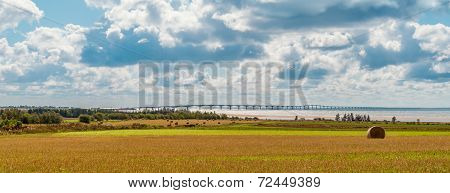 Panorama Of Hay Bales On A Farm Along The Ocean With The Confederation Bridge In The Background