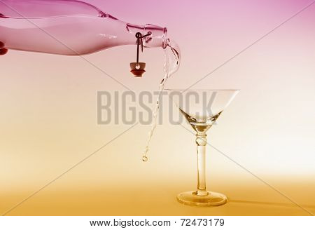 Clear Water Pour Out Of Bottle Splash Into Glass And Spill With Pink And Yellow Back Lighting