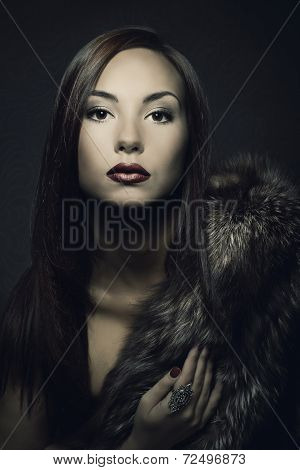 Woman Beauty Portrait In Luxury Fur Coat. Dark Background.